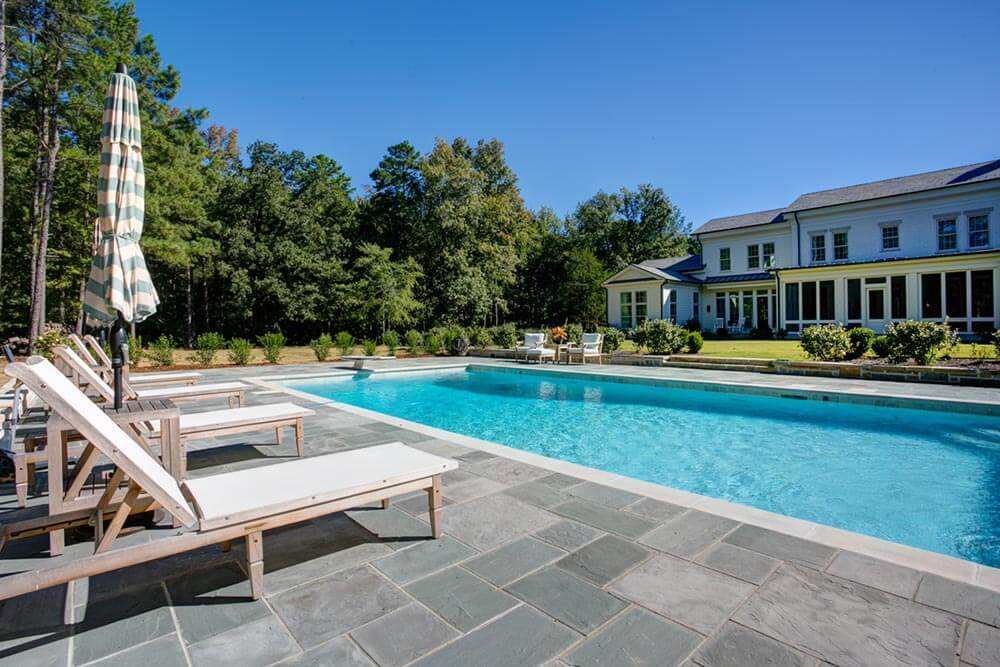 Deep Blue Pool on Sunny Summer Day Outside a Greek Revival Inspired Home in Little Rock