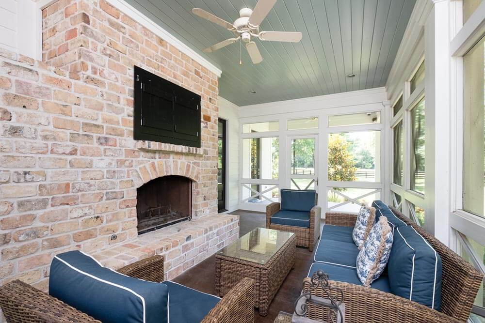 Side porch with a fireplace, whicker couches, and a TV
