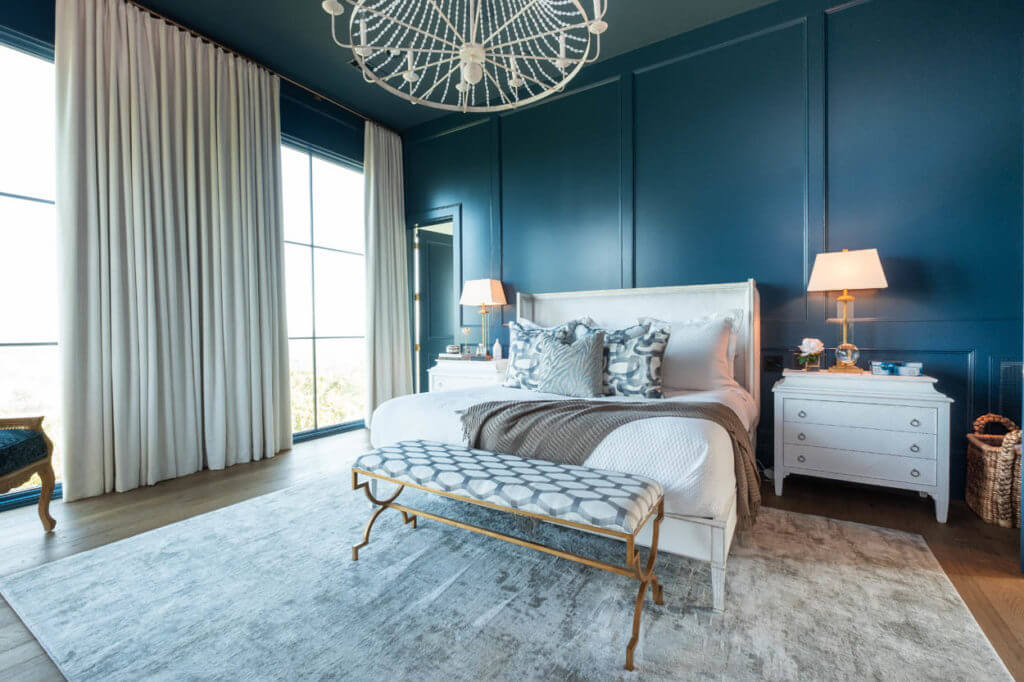 Beautiful, deep blue walls with matching casing. Beige floor to ceiling drapes covering floor to ceiling windows. Classical white furniture with gold accents.
