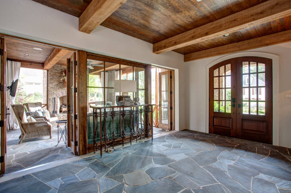 Beautiful dark wood ceiling with large exposed joists. Flooring is a dark bluish-green stone.