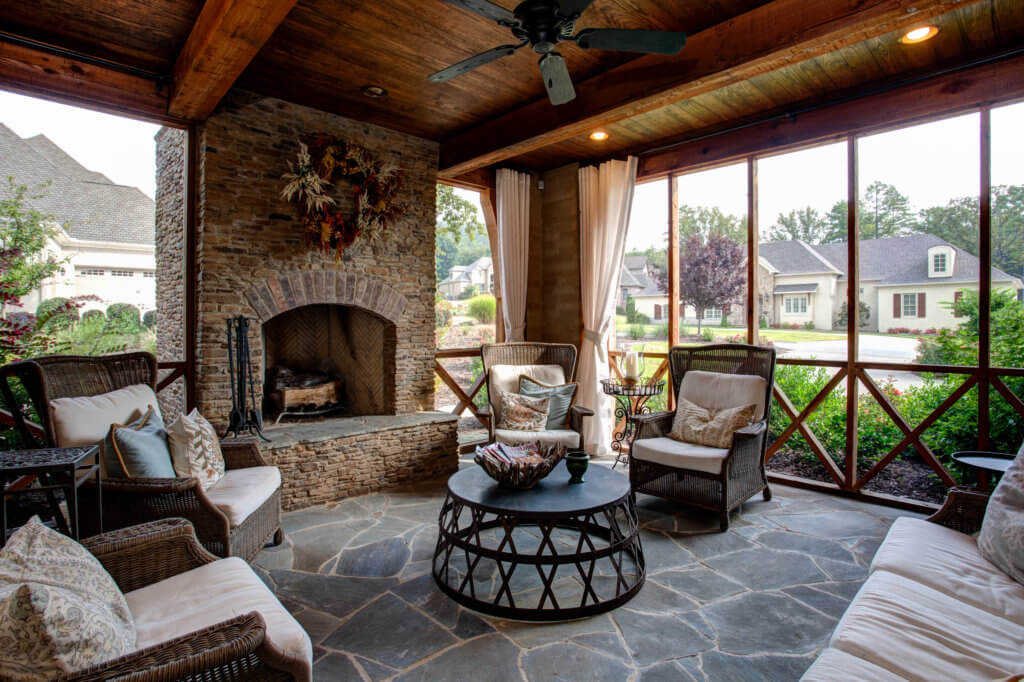 Outdoor sitting area with large fireplace clad in the same small stone masonry found on the front of the house