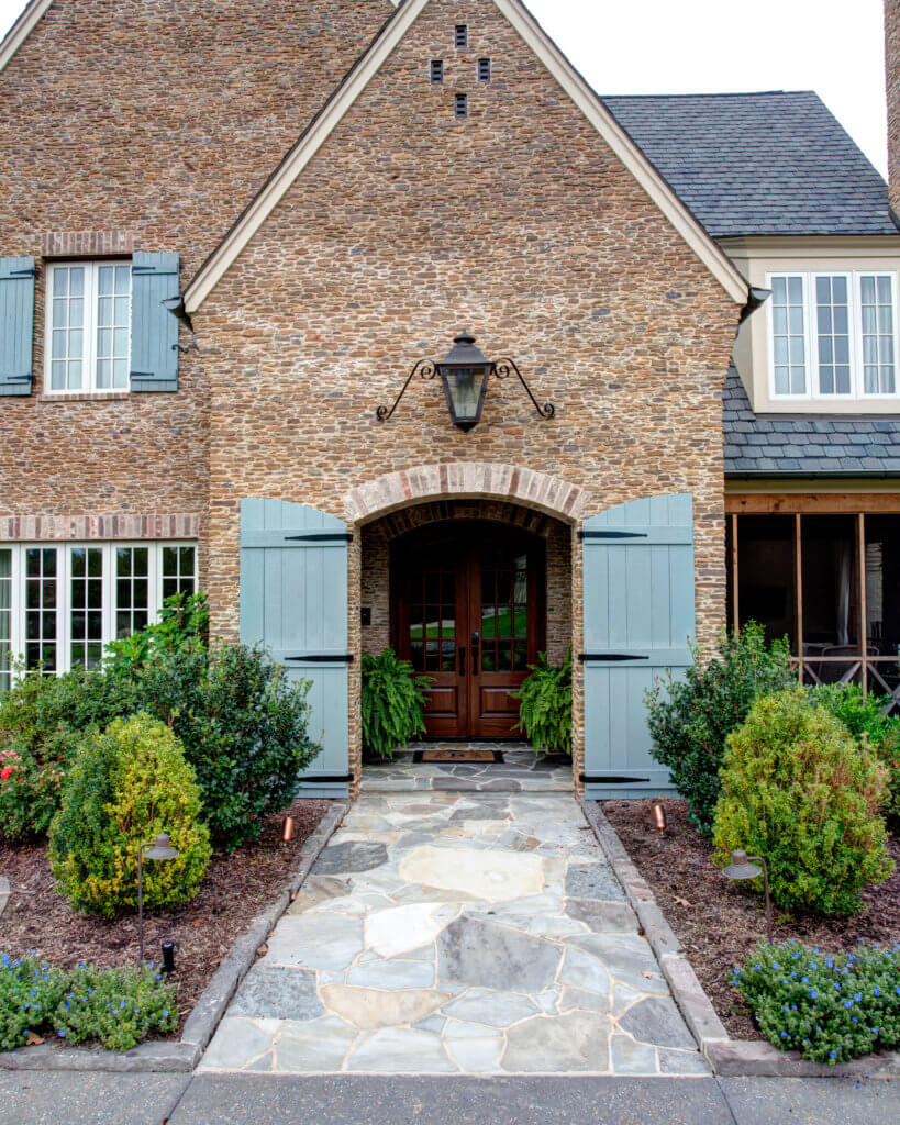 Front Entry way composed of small stone masonry. French front door with 16 panes of glass each. Door is dark stained wood.
